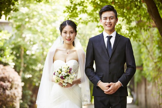 outdoor portrait of a newly-wed asian couple