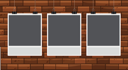 Three pictureframes on brickwall