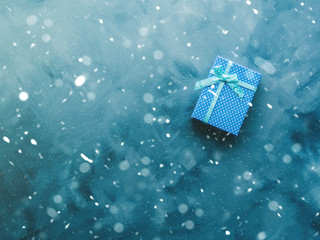 Gift box flat lay with snow flakes on blue background. Holiday surprise concept