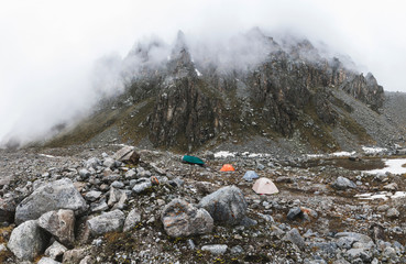Camping with tents high in the mountains in winter. Fog, snow and cold weather. Mountain range and rocks on background