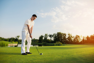 A man in a white suit plays golf. He is preparing for another ball hit