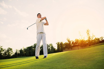 Great blow. A man in a white suit plays golf. he is pleased with his blow