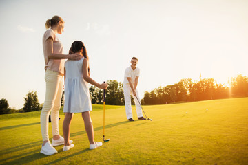 Poster Golf Family playing golf at sunset. A woman and a girl are looking at a man who is preparing to make a hit