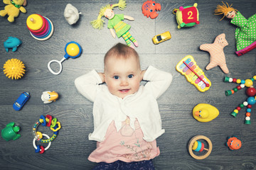 cute baby girl with lot of toys on the floor. top view