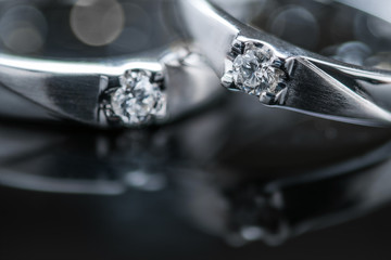 Close up pair of Platinum wedding rings with diamond on bokeh reflection background