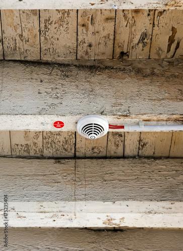 Rauchmelder mit elektrischer Verkabelung an alten Holzbalken in ...