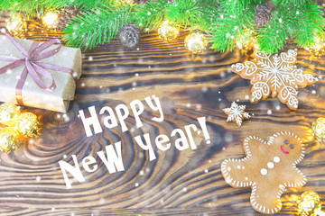 Christmas fir tree with homemade gingerbread cookies, gift and lights on old wooden background with space for text. Merry Christmas and Happy New Year. Xmas concept. Top view. Copy space.