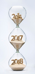 Passing into New Year 2017, 2018. Past, present and future concept. 3 part hourglass. Falling sand taking the shape of years 2016, 2017 and 2018.