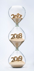 Passing into New Year 2018, 2019. Past, present and future concept. 3 part hourglass. Falling sand taking the shape of years 2017, 2018 and 2019.