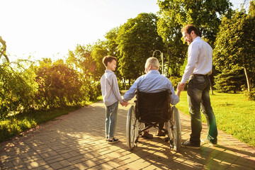The old man in a wheelchair, his son and grandson are walking in the park