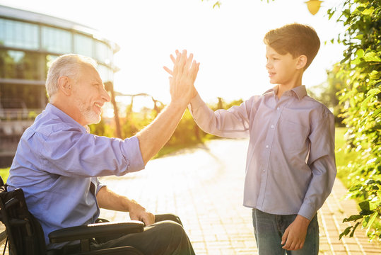 High five. The old man in a wheelchair greets his grandson