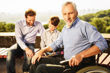 An old man in a wheelchair posing against his son and grandson
