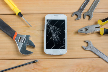 Mobile phone next to tools on wooden background. service, repair concept