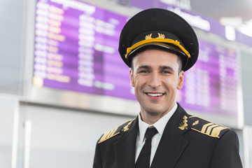 Happy smiling aviator glancing ahead in airport