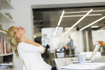 Businesswoman in the office taking a break and doing a neck exercise