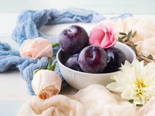 Blue plums in bowl with pink flowers. Summer autumn fruit