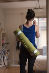 Rear view of woman with exercise mat talking on phone