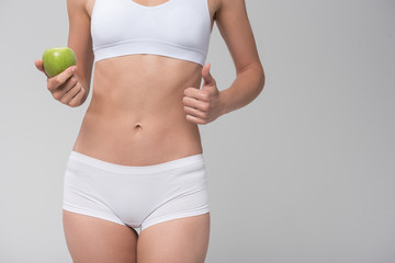 Thin young woman prefers to eat fruits