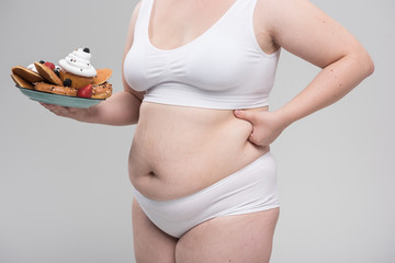 Thick figure of girl eating pastry