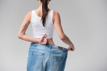 Thin young woman presenting result of diet