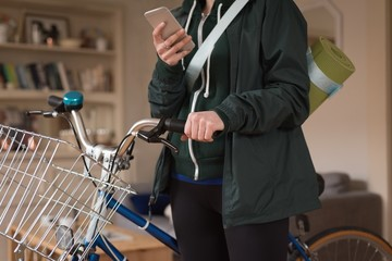 Mid section of woman with bicycle using phone