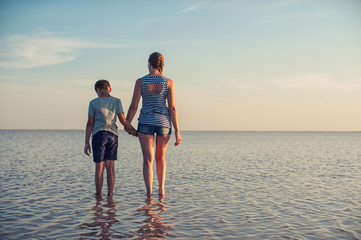 Mother and her son on salty lake with beauty sunset