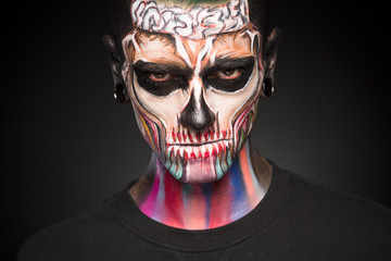 Close up portrait of mans face with colored skeleton makeup. FAce art, professional zombie face makeup.