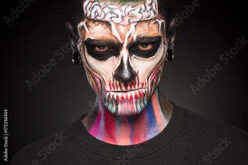close up portrait of mans face with colored skeleton makeup face art professional zombie