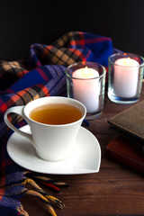 A cup with a hot tea drink on a wooden background with an autumn plaid, cones,