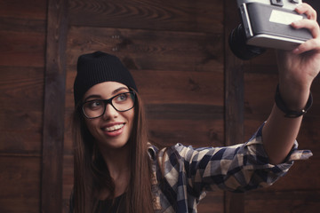 Hipster girl in glasses and black beanie with vintage camera