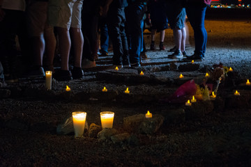 Rocks on the ground at a candlelight vigil spell out RIP.