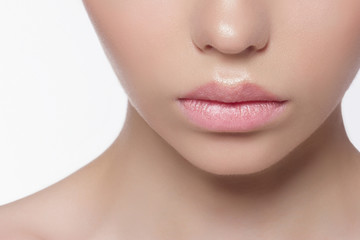 The macro photo of the closed female mouth with a natural shade of lips. Demonstration of care of skin of lips. Cosmetology, Spa, cosmetics, injections