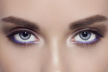 The macro photo of blue female eyes with a fashionable make-up, long eyelashes and equal dense eyebrows. Correction of eyebrows, sight, cosmetology, lenses, extension of eyelashes, permanent make-up