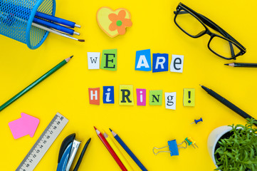 WE ARE HIRING CONCEPT ON yellow work place, office background with supplies