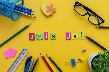 JOIN US - CONCEPT text on yellow work place, office background with supplies