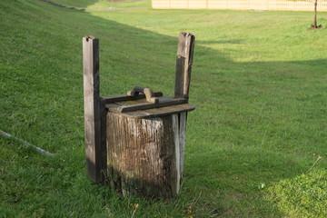 Старый, заброшенный, деревянный круглый колодец на зелёной поляне.