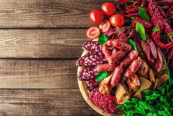 Food tray with delicious salami, pieces of sliced ham, sausage, tomatoes, salad and vegetable.