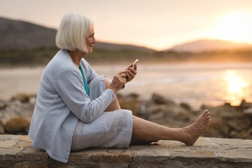 Senior woman sitting on wall and using mobile phone at beach