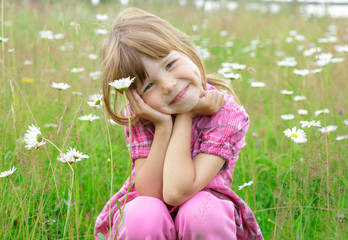 Small girl on camomile field
