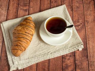 Breakfast croissant and tea on a textile napkin. Dark wooden background.