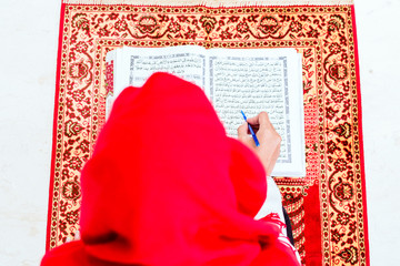 Asian Muslim woman reading Koran or Quran on praying carpet wearing traditional dress