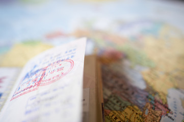 (Selective focus) A passport with entry stamps is on a blurred geographical map of the world.