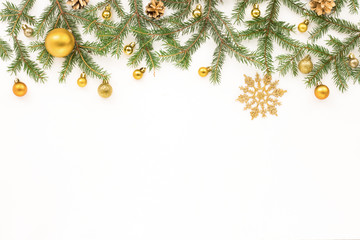 Christmas spruce branches, golden christmas decorations on white background, flat lay, top view.