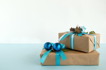 Two Christmas gift boxes wrapped of craft paper, blue and white ribbons, decorated of fir branches, pine cones and Christmas balls on the blue and white background. Copy space.