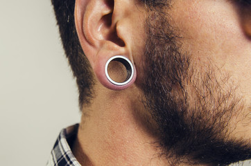 Closeup of hipster ear, with hole earring.  Wall mural