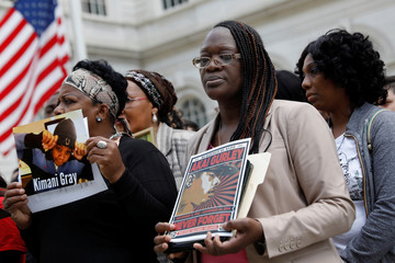 Family members whose relatives were killed in encounters  with the NYPD stand before taking a knee with others to show solidarity with NFL players on the steps of City Hall in New York