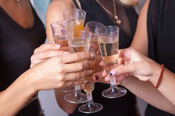 Close up photo of hands holding wineglasses with champagne	Small group of young woman is celebrating something. They hold wineglasses in theirs hands. Champagne and juice are in the wineglasses.