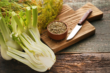 Ripe fennel bulbs and dry seeds in bowl on wooden table