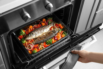 Woman cooking fish with vegetables in oven