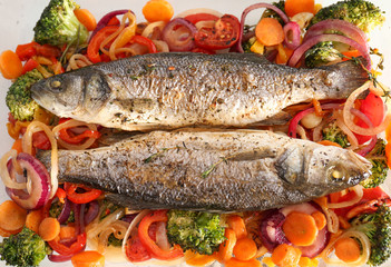 Tasty baked fish with vegetable garnish, top view